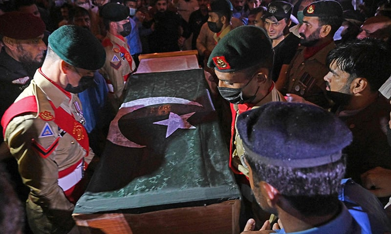 Soldiers prepare to place the flag-draped coffin of Dr Abdul Qadeer Khan during his funeral outside the Faisal Mosque in Islamabad on October 10. — AFP