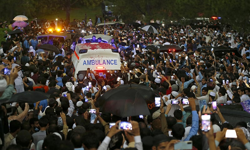 People move with an ambulance carrying the casket of Dr Abdul Qadeer Khan following his funeral prayers in Islamabad. — AP