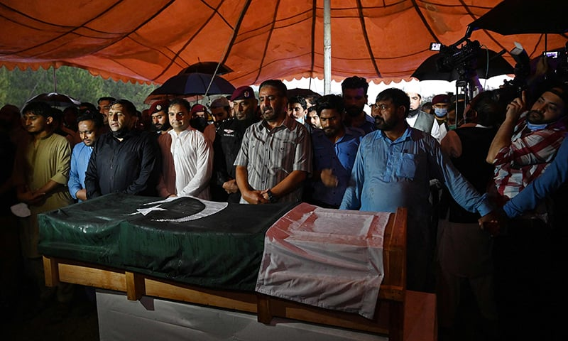 Officials and residents offer prayers next to the coffin of Dr Abdul Qadeer Khan during his funeral in Islamabad on October 10. — AFP