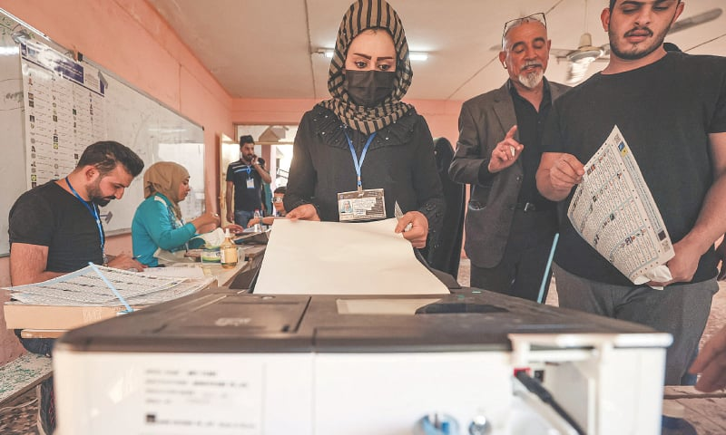 BAGHDAD: A woman casts her vote at a polling station on Sunday.—AFP