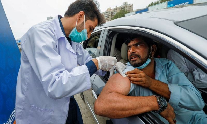 In this file photo, a resident receives a vaccine dose against Covid-19 at a drive-through vaccination facility in Karachi. — Reuters/File