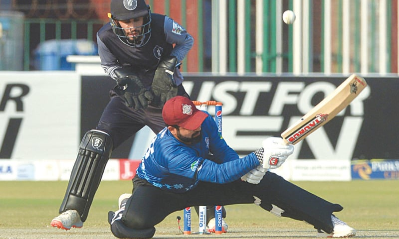 Southern Punjab's Tayyab Tahir attempts a daring shot during his knock of 78 as Khyber Pakhtunkhwa wicket-keeper Mohammad Haris watches in the National T20 Cup match at the Gaddafi Stadium on Sunday. —M. Arif/White Star