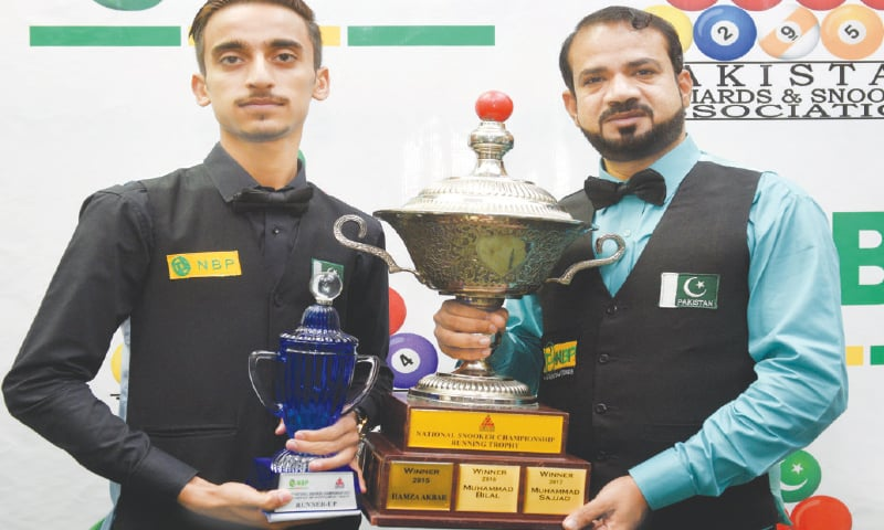 Mohammad Sajjad (R) and Ahsan Ramzan (L) pose with their trophies after the National Snooker Championship final on Monday.—Tahir Jamal/White Star