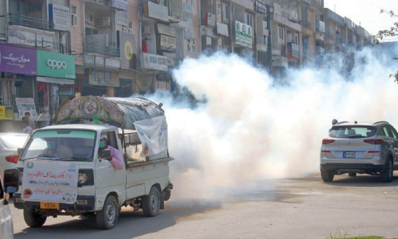 MCI's health directorate carries out anti-dengue fumigation in a street in G-11 on Monday. — Online