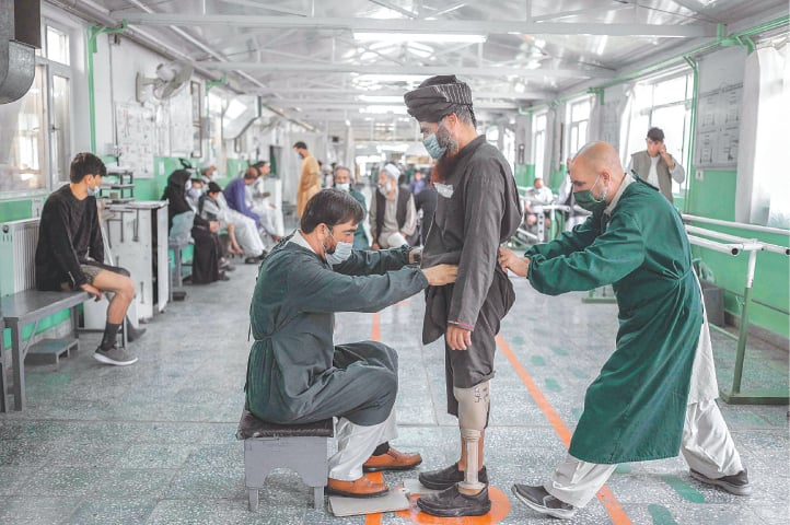 WORKERS at a rehabilitation centre run by the International Committee of Red Cross help a Taliban member who claims to have lost his leg during a US air strike in Kabul.—AFP