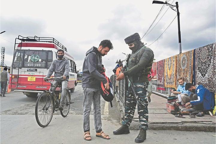 A SECURITY man checks the bag of a pedestrian along a street in Srinagar on Monday.—AFP
