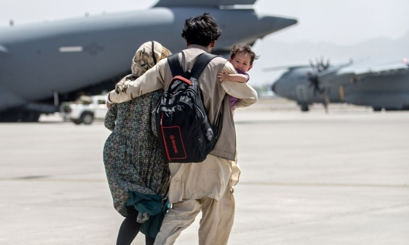 A family walks towards a US Air Force Boeing C-17 Globemaster III during an evacuation at Hamid Karzai International Airport on August 22. — Reuters