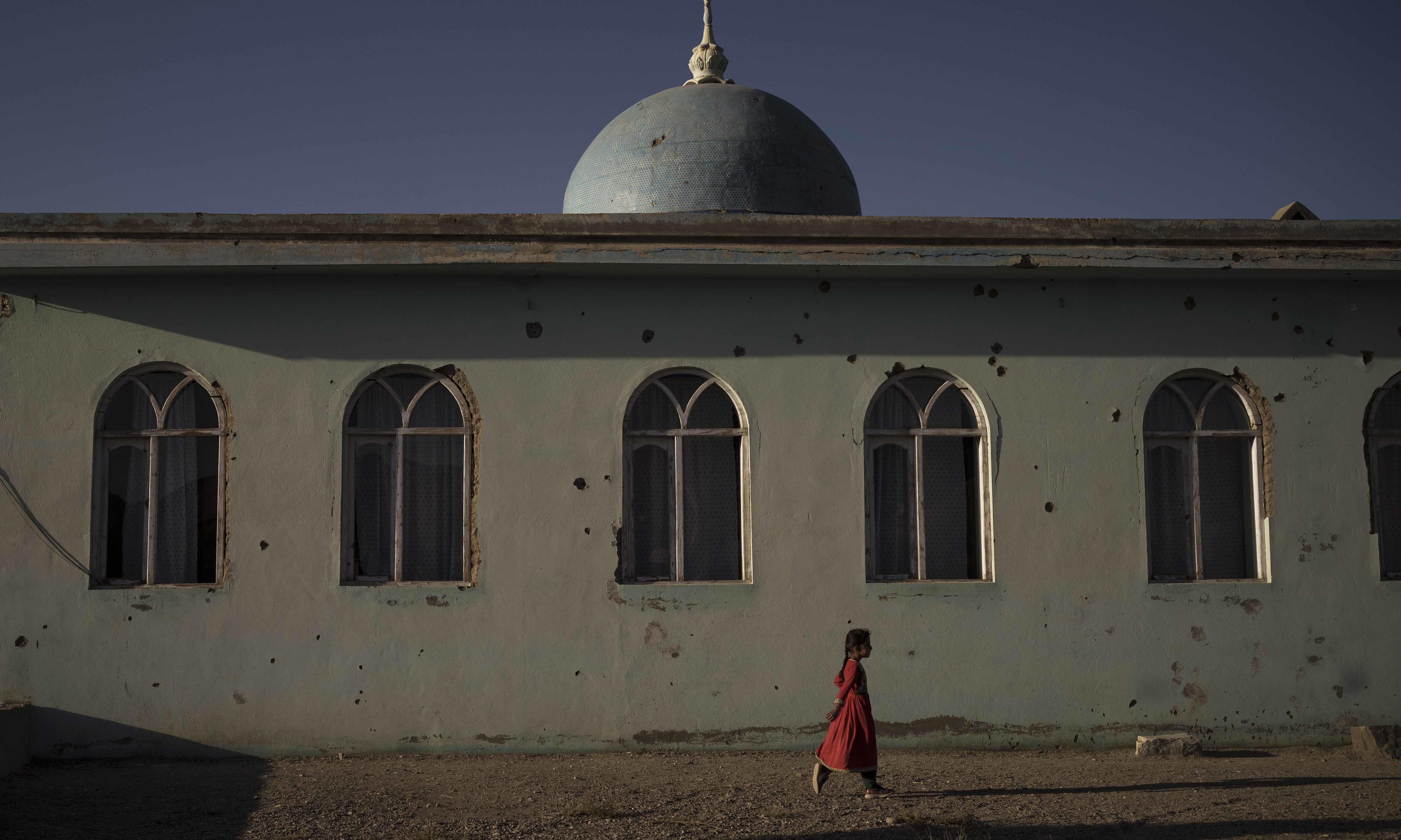 An Afghan girl walks outside a mosque marked by bullet holes at a village in Wardak province on October 11. — AP