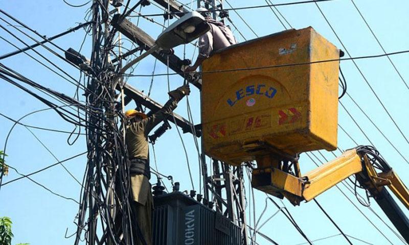 A Lesco staffer installs a new transformer near Ferozpur Road in Lahore. — APP/File