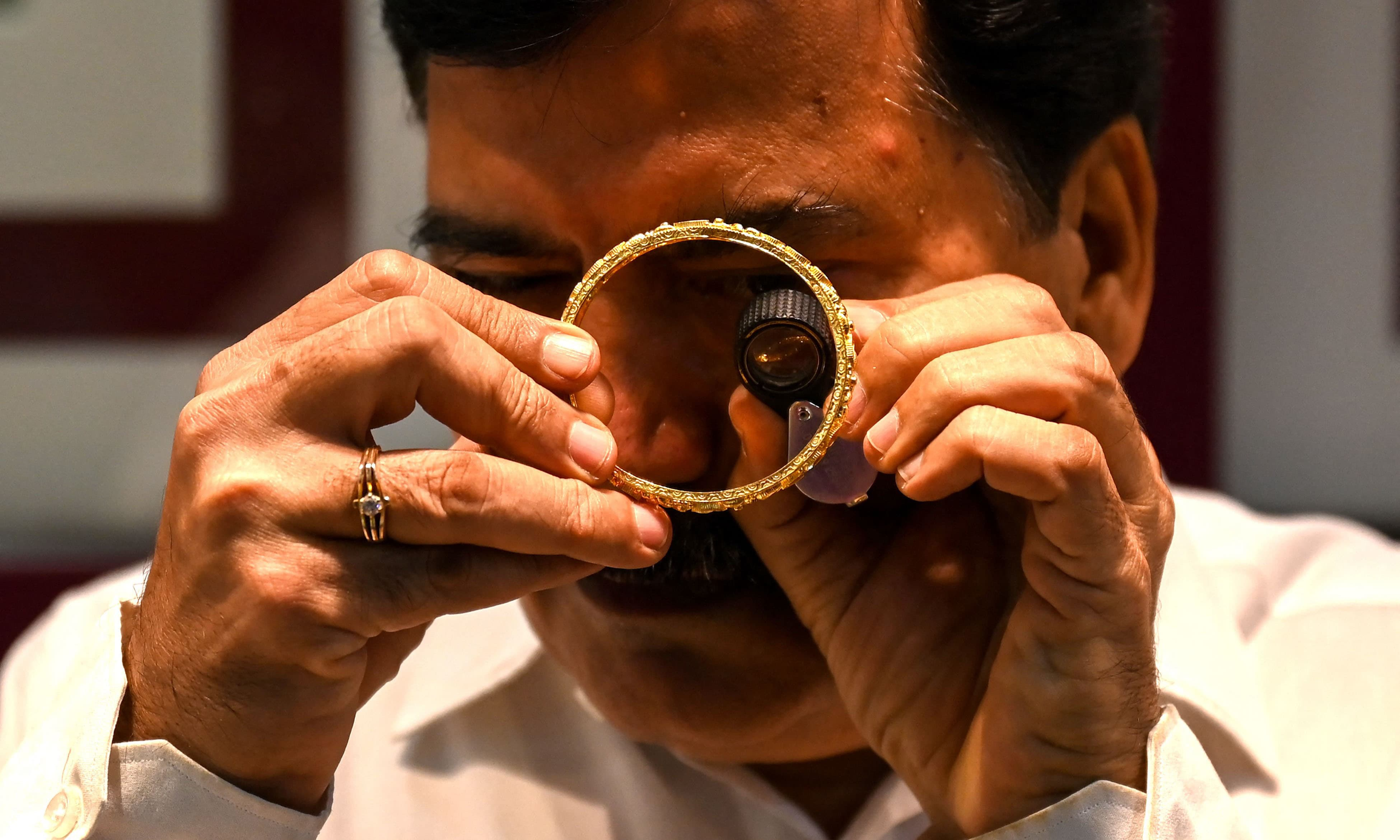 This picture taken on August 11 shows a shop manager handling gold bracelets at a jewellery shop in Mumbai. — AFP