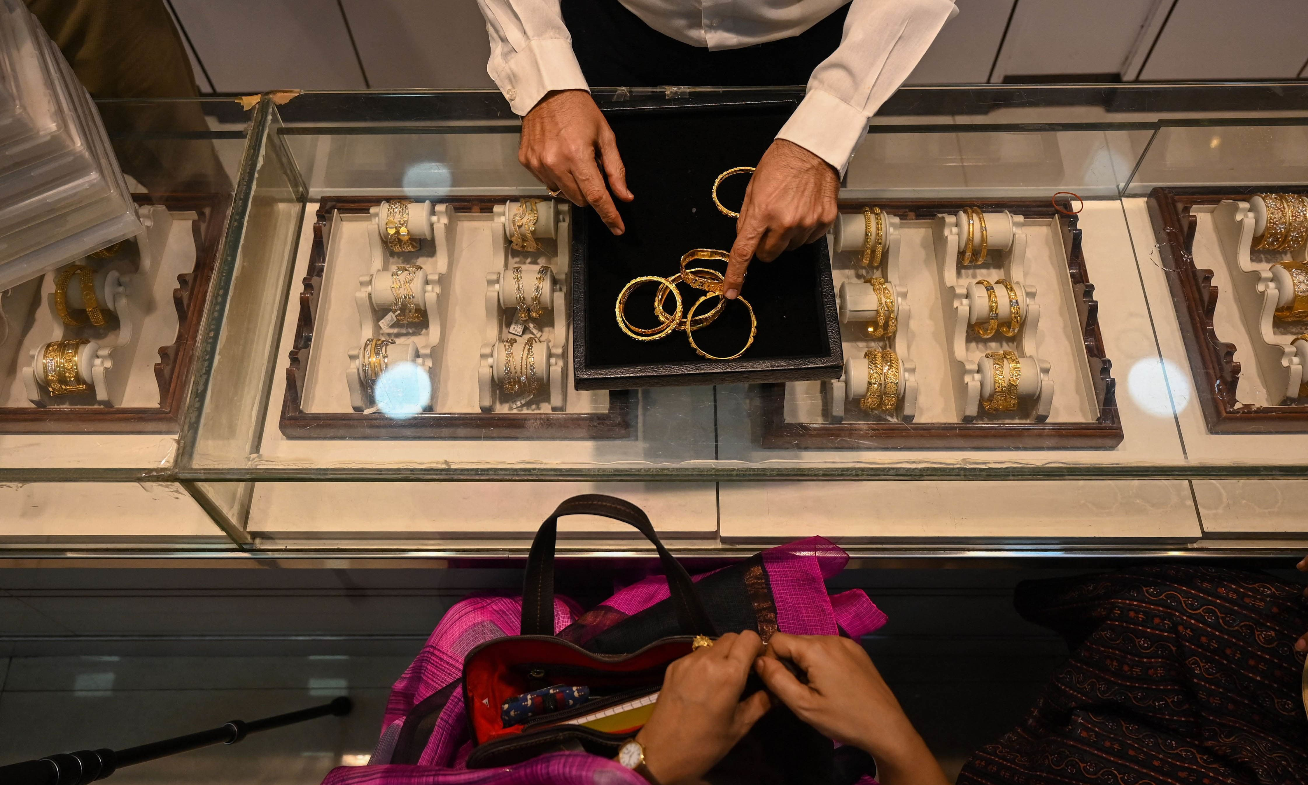 This picture taken on August 11 shows a shop manager speaking with customers at a jewellery shop in Mumbai. — AFP