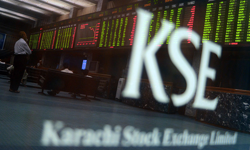 Pakistani stockbrokers watch the latest share prices on a digital board during a trading session at the Karachi Stock Exchange (KSE) in Karachi on May 28, 2013. — AFP