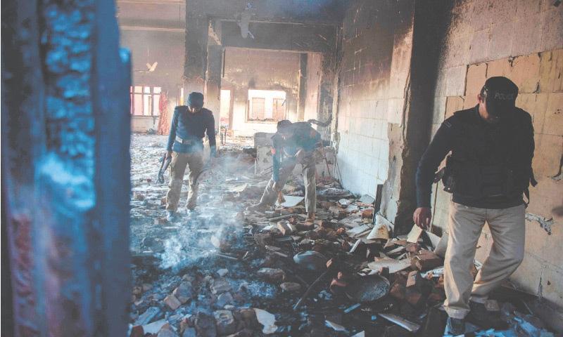 Policemen inspect the burnt-out Hindu shrine in Karak district on Jan 1. — AFP/File