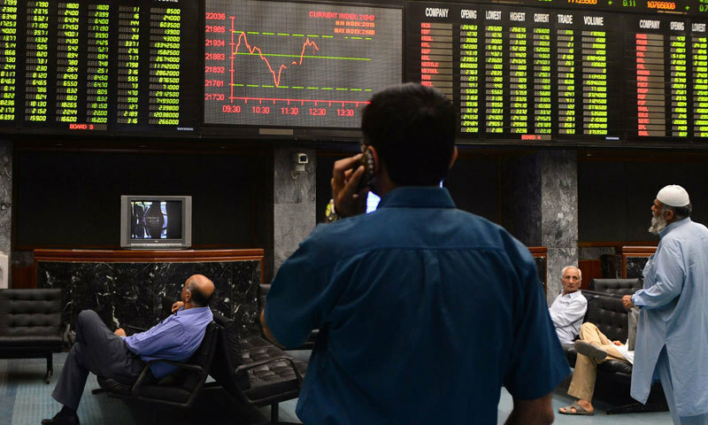 A man speaks on his cellphone in this file photo as he watches share prices on a screen at the Pakistan Stock Exchange (PSX) in Karachi. — AFP/File
