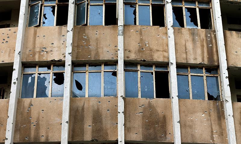 فائرنگ سے گھروں کی کھڑکیوں کے شیشے ٹوٹ گئے اور دیواروں میں سوراخ ہو گئے— فوٹو: اے پی