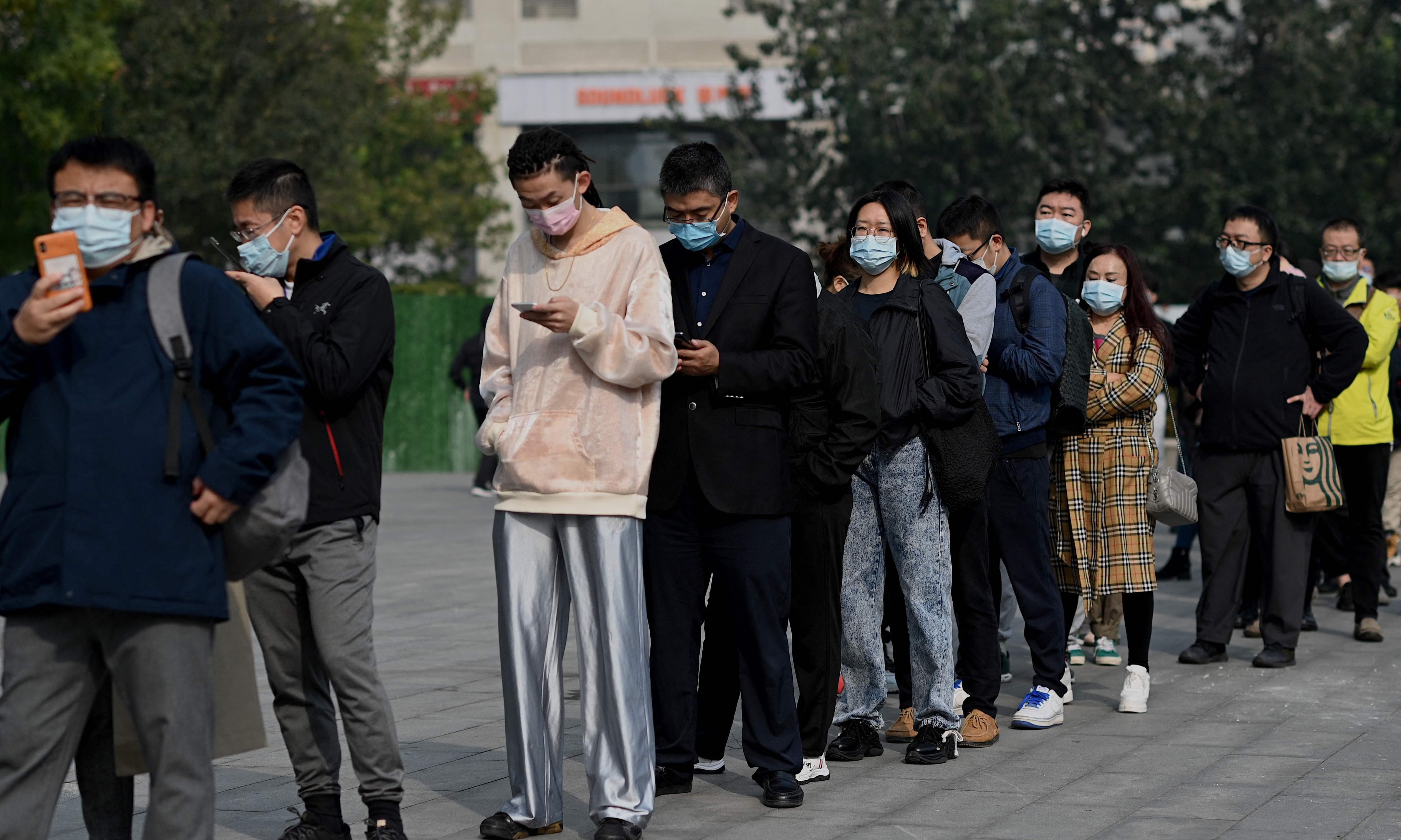 People wait in a queue to be tested for the coronavirus at a nucleic acid collection station in Beijing on October 25. — AFP