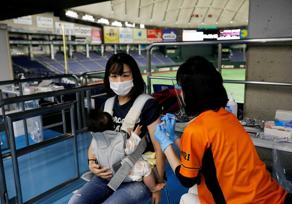 A woman receives a dose of the coronavirus vaccine at Tokyo Dome, Tokyo, Japan, August 16. — Reuters