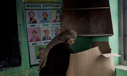 An elderly Kashmiri woman casts her vote at a polling station set up inside a school. — Photo by AP