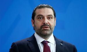 Hariri returns home, shelves resignation