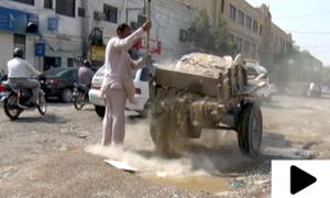 کراچی میں سڑک کے گڑھے بھرنے کا بیڑا گدھا گاڑی والے نے اٹھا لیا