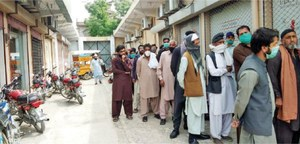 People fail to keep distance outside banks in Taxila