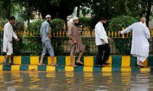 In pictures: Rain brings respite from suffocating heat to Karachi, along with the usual miseries