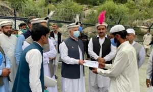 CM gives away compensation cheques in Chitral