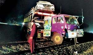 Trailer carrying cars gets stuck on railway track