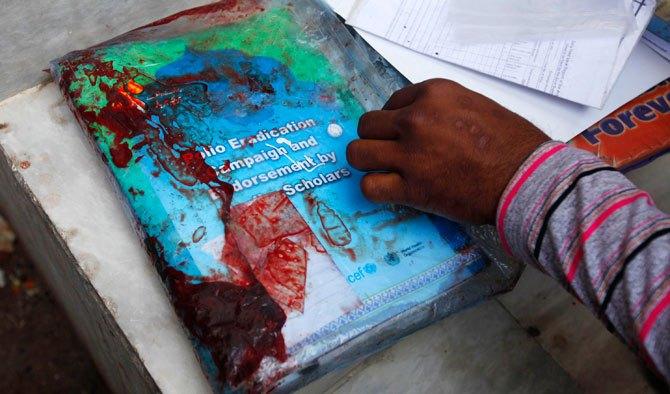 کراچی میں ایک ریسکیو اہلکار حملے کے نتیجے میں متاثر ہونے والی خاتون نسیمہ بی بی کے سامان کا دیکھ رہا ہے۔ رائٹرز فوٹو۔