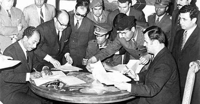 شام کے صدر حافظ الاسد ( دائیں جانب بیٹھے ہوئے) اٹھارہ اپریل 1971 کو مصری صدر انورالسادات ( بائیں جانب بیٹھے ہوئے)، لیبیا کے معمر قذافی ( درمیان میں بیٹھے)  بن غازی لیبیا کے مقام پر فیڈریشن آف عرب ریپبلک کے معاہدوں پر دستخط کررہے۔ تاہم ان تین عرب ممالک کے درمیان یہ معاہدہ عمل پذیر نہ ہوسکا۔ تصویر بشکریہ آن لائن میوزیم آف سیرین ہسٹری