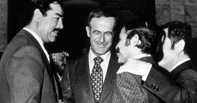 شامی صدر حافظ الاسد درمیان میں ہے جبکہ بائیں جانب اس وقت عراق کے نائب صدر صدام حسین موجود ہیں۔ سیدھے ہاتھ پر الجزائر کے وزیرِ خارجہ عبدالعزیز ہیں اور دور دائیں جانب شام کے نائب صدر عبدالاالحلیم خدام  بغداد میں عرب لیگ اجلاس میں موجود ہیں۔ تصویر بشکریہ آن لائن میوزیم آف سیرین ہسٹری