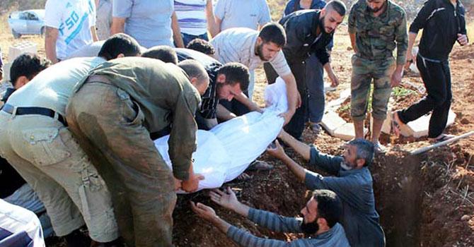 شامی اپوزیشن کے خبر رساں شام نیوز نیٹ ورک کی جانب 15 جولائی 2012 کو جاری کردہ اس تصویر میں شامی حمس شہر میں بابا امر کے مقام پر ایک لاش کو دفنایا جارہا  ہے۔ تصویر اے ایف پی