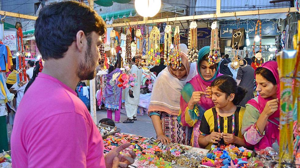 عید الاضحیٰ کے موقع پر خواتین اور بچے خریداری کرتے ہوئے۔ فوٹو اے پی پی