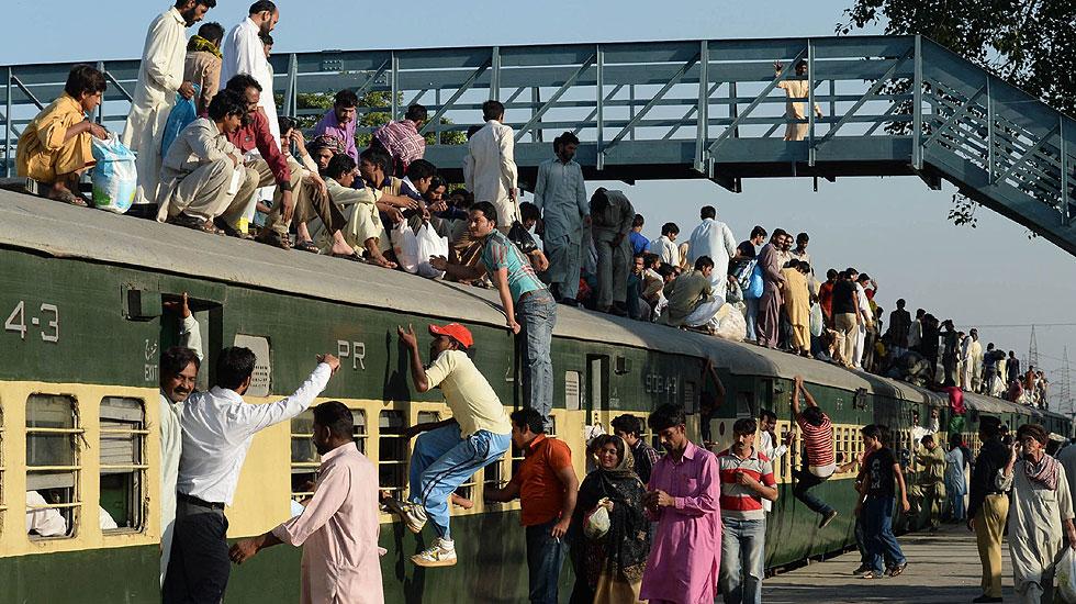 عید اور تہواروں پر ٹرینوں اور بسوں میں شدید رش کے باعث لوگوں چھتوں پر سفر کرنے کے ساتھ ساتھ لٹک کر یہ مرحلہ طے کرنے کا خطرہ بھی مول لیتے ہیں۔ فوٹو اے ایف پی